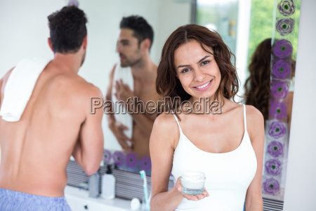 happy woman holding cream while husband