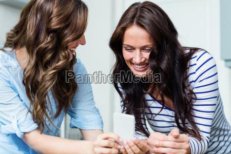 smiling female friends using mobile phone