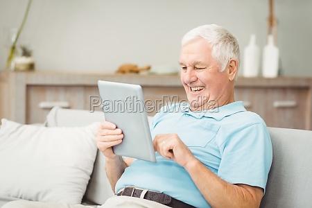 happy senior man using digital tablet