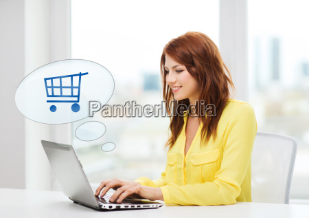 smiling woman with laptop computer shopping