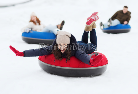 group of happy friends sliding down