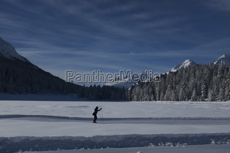person skiing on across snowy landscape