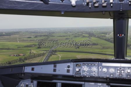 field seen through airplane windshield