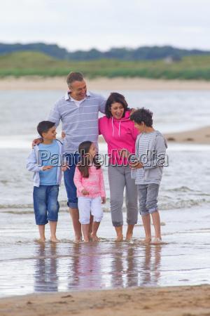 grandparents and grandchildren smiling on beach