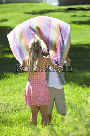 couple lying picnic blanket in field