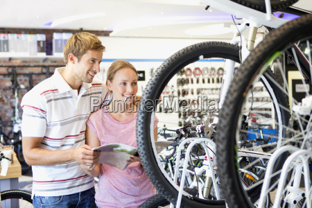 couple choosing a bicycle in shop