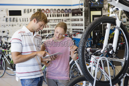 store manager assisting customer in bicycle