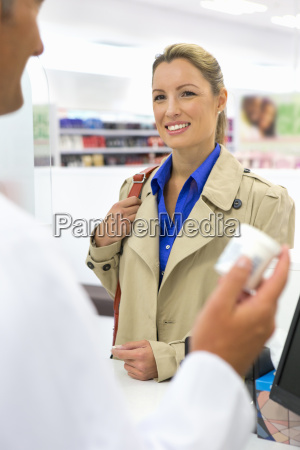 smiling female customer purchasing medication from