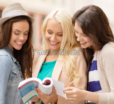 beautiful girls with city guide book