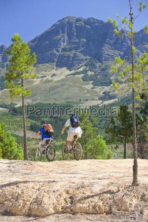 senior couple mountain biking on mountain