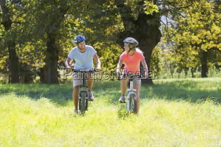couple mountain biking in treelined field
