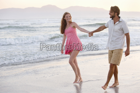 couple holding hands walking on sunny
