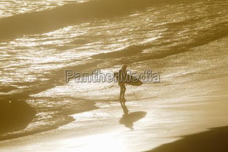 man holding surfboard walking along beach