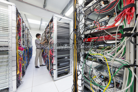 technician checking cables in server room