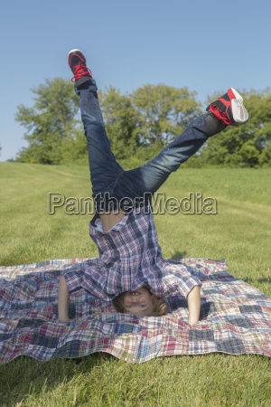 boy doing headstand at backyard during
