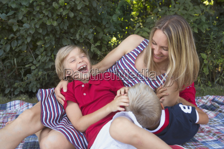 playful mother and sons in backyard