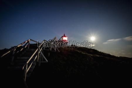 steps leading towards illuminated lighthouse during