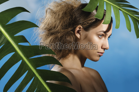 thoughtful naked woman with palm leaves