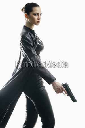 female spy with gun walking against