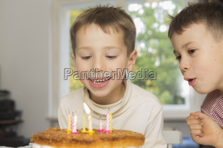 boy looking at brother blowing birthday