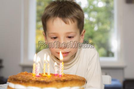 cute birthday boy looking at candles