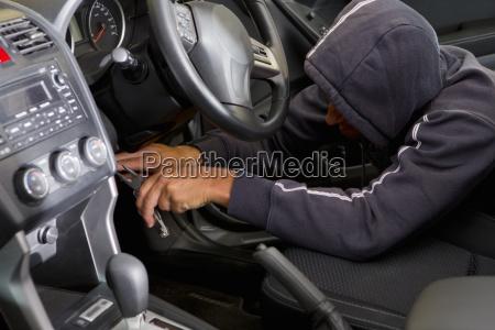 car thief hotwiring car to steal