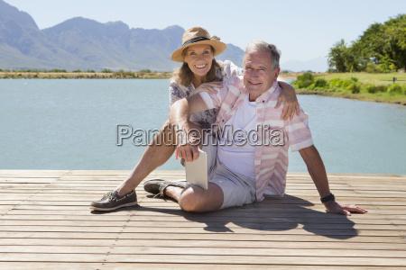 senior couple sitting on wooden jetty