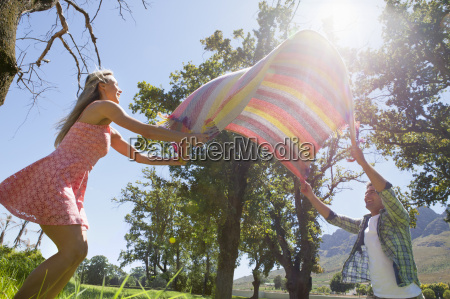 couple laying picnic blanket in field