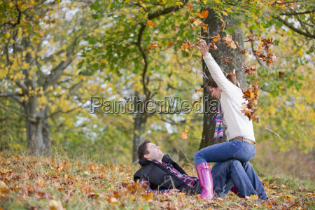 couple playfully throwing leaves in autumnal