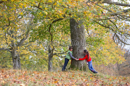 young boy and girl hugging tree