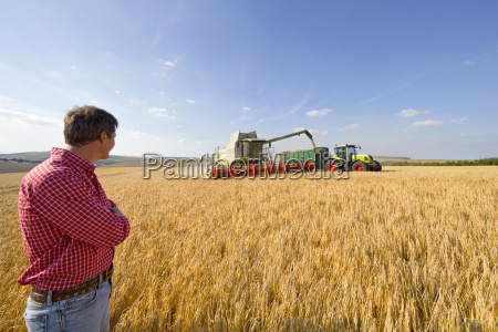 farmer watching combine harvester fill tractor