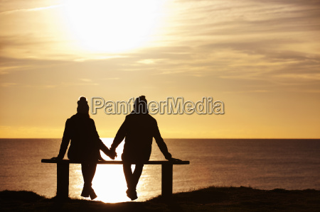 silhouette of couple sitting on bench