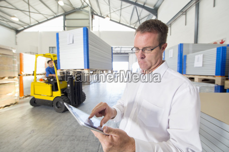portrait of businessman checking digital tablet