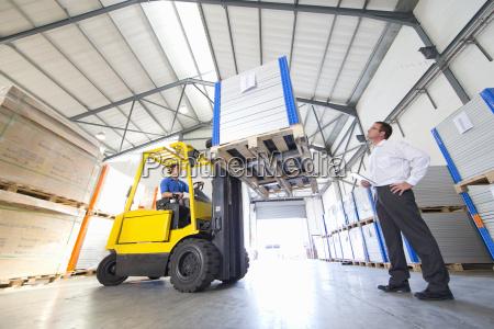 businessman supervising forklift truck driver worker