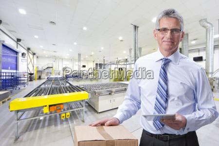 portrait of smiling businessman holding digital
