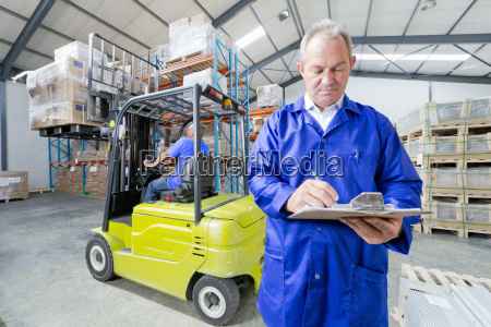 warehouse supervisor worker checking clipboard in