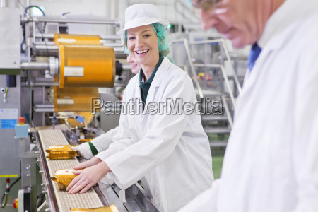 portrait smiling worker stacking cheese on