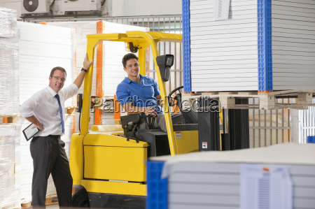 businessman smiling at camera supervising forklift