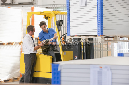 businessman supervising forklift truck driver in