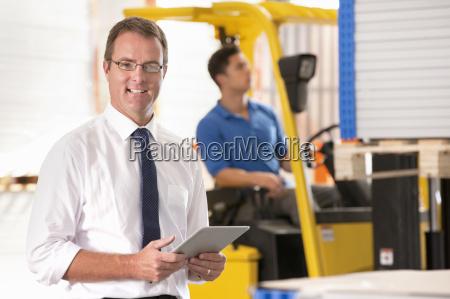 businessman looking at camera supervising forklift