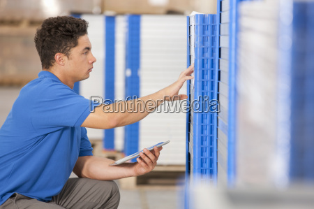 warehouse worker checking solar panels with