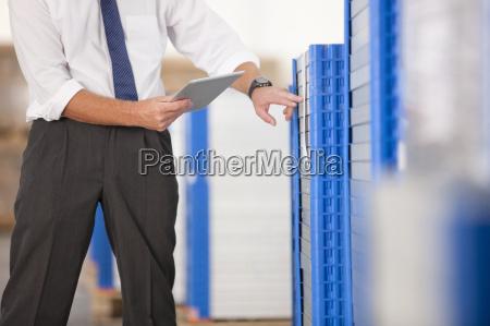 businessman checking solar panels with digital