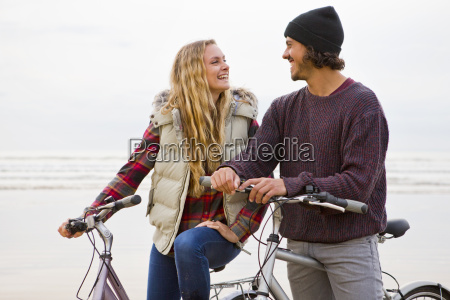 smiling couple with bicycles talking face