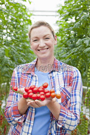 portrait smiling grower holding ripe red