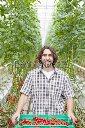 portrait smiling grower holding crate of