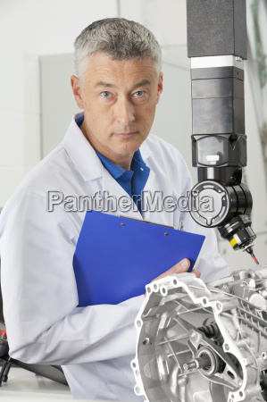 portrait of serious engineer holding clipboard