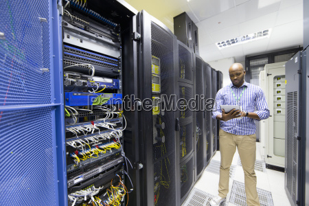technician checking digital tablet in server
