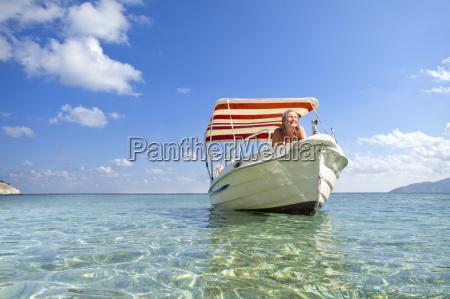 smiling woman sunbathing on boat in