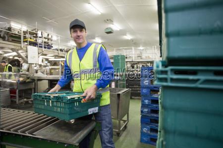 portrait worker lifting bin of packaged
