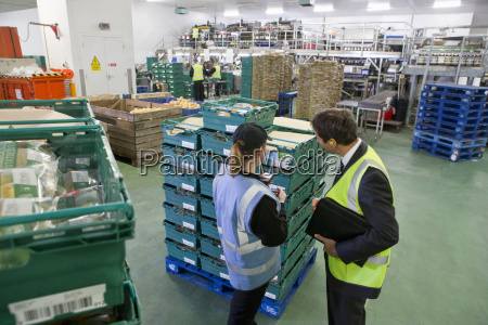 supervisor and worker examining stacked bins